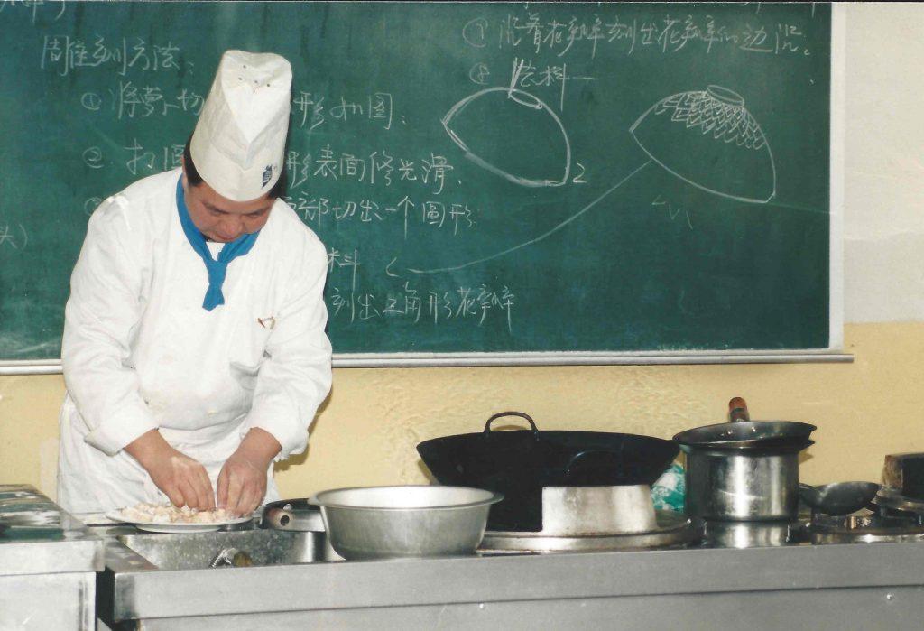 Kokkemesterlæreren underviser i tilberedningen af kylling og grønt i sur/sød sauce