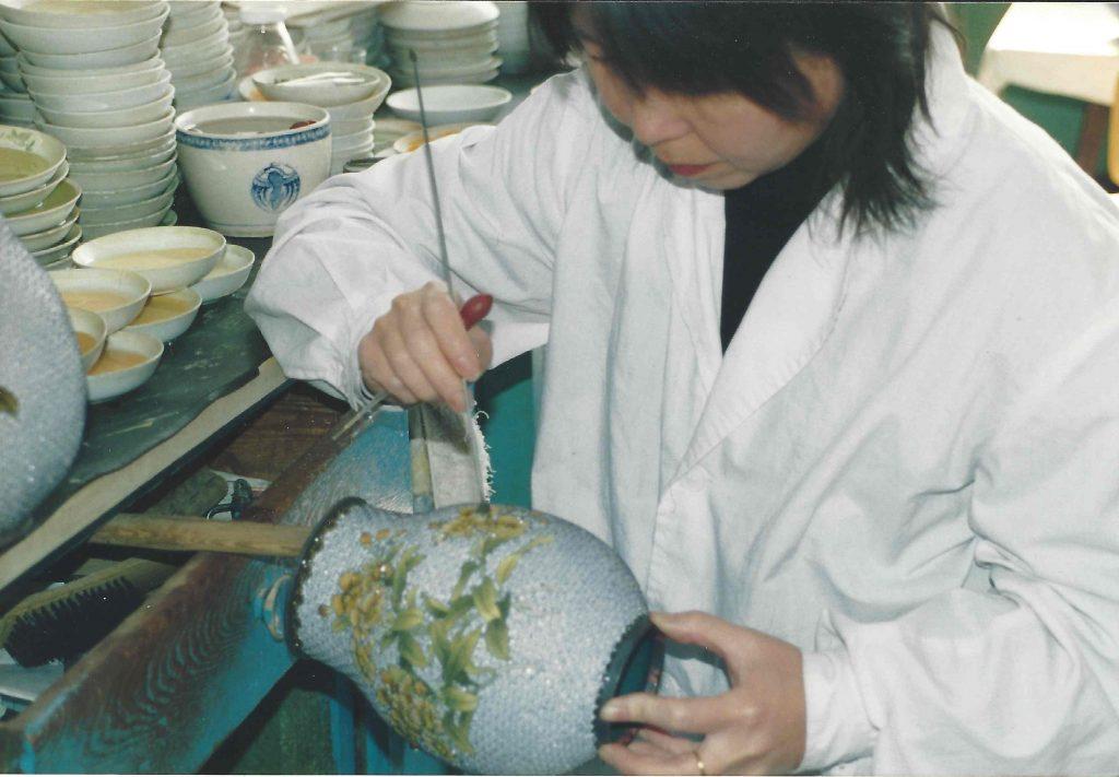 Cloisonné-kunstneren udfylder de mange mønstre med emalje