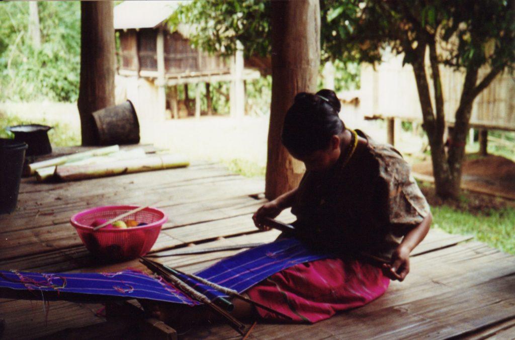 En Karen-kvinde væver stoffer i stammens farver